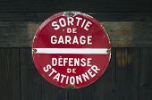stock photo of garage  - French sign on wooden garage door warning that no parking is allowed in front of the garage exit - JPG