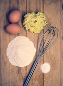 stock photo of raw materials  - Eggs flour and other raw materials on a wooden board - detail from kitchen in retro colors ** Note: Visible grain at 100%, best at smaller sizes - JPG
