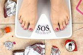 stock photo of sos  - Feet on bathroom scale with word SOS and junk food garbage - JPG