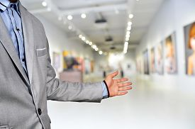 picture of asset  - Artist or Photographer or Manager welcome guest to his image exhibition show in art gallery or museum as conceptual of asset management - JPG