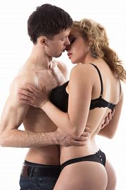 stock photo of half naked  - Young half naked couple love play on the distance of a kiss guy in jeans caressing girl in black underwear studio shot white background - JPG