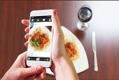 picture of meatball  - Hand holding smartphone against overhead view of spaghetti and meatballs with basil leaf - JPG