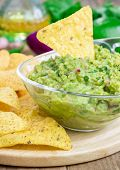 stock photo of nachos  - Bowl with chunky guacamole served with nachos and ingredients on backgroung - JPG