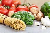 image of basil leaves  - Italian cuisine ingredients of spaghetti basil leaves garlic mushrooms peppers and fresh tomatoes with extreme shallow depth of field - JPG