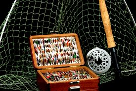 picture of fly rod  - Traditional Fly Fishing Rod Reel Net and Flies in Old Wooden Box Against a Black Background - JPG