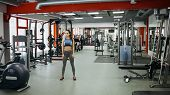 Sporty Woman Standing With Arms Down In Fitness Gym. poster
