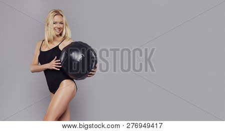 poster of Young Happy Fitness Blonde Girl With Sporty Body Posing At Studio With Fitness Ball. Beautiful Fit G