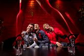 image of bachelor party  - Three men sitting in front of dancing woman - JPG