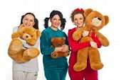stock photo of pyjama  - Three women in pyjamas holding teddy bears and smiling isolated on white background - JPG