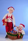 Happy New year. Charming Santa helpers. Little boy and a girl dressed as Santa bring Christmas gifts