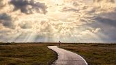 A Person Walking Alone Along S-shape Path. The Sun Produces Amazing Light Rays Across The Sky. The I poster