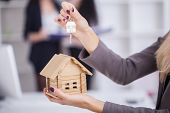 Salesman Carrying A Model House In Hand Is Delivering The House Key To The Buyer, Customers Receive  poster