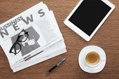 Elevated View Of Cup Of Coffee, Pen, Tablet With Blank Screen And Business Newspapers On Wooden Tabl poster