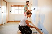 Couple Decorating Room In New Home Painting Wall Together poster