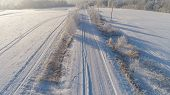 Aerial View Winter Landscape Countryside Road Through Winter Field With Forest. Winter Forest On A S poster