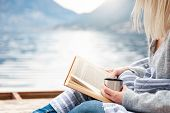Girl Is Reading Book On Wooden Pier By Winter Sea, Mountains, Beach. Cozy Picnic With Hot Steamy Bev poster