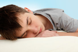 picture of teenage boys  - Closeup of a teen boy sleeping on a bed - JPG