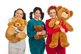 picture of pyjama  - Three women in pyjamas holding teddy bears and smiling isolated on white background - JPG