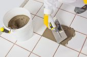 picture of mortar-joint  - Worker With Trowel Repairs Old White Tiles With Tile Adhesive - JPG