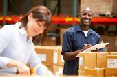 stock photo of warehouse  - Workers In Warehouse Preparing Goods For Dispatch - JPG