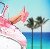 stock photo of car-window  - Summer vacation travel freedom concept with cool convertible vintage car and woman feet out of window against tropical sea background with palm trees - JPG