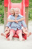 stock photo of skid  - Smiling an d happy senior couple at the beach - JPG