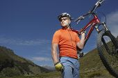 stock photo of spandex  - Male cyclist carrying bike against hills and blue sky - JPG