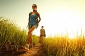 stock photo of greenery  - Two ladies hikers walking through green lush meadow - JPG