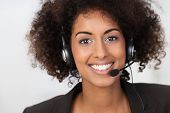 picture of vivacious  - Close up facial portrait of a beautiful vivacious African American businesswoman wearing a headset smiling at the camera conceptual of client services support or a call centre operator - JPG