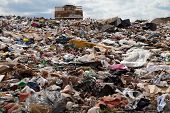 stock photo of landfill  - Truck managing garbage in a landfill site - JPG