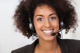 stock photo of vivacious  - Close up facial portrait of a beautiful vivacious African American businesswoman wearing a headset smiling at the camera conceptual of client services support or a call centre operator - JPG