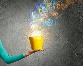 foto of fumes  - Close up of female hand holding bucket with colorful fumes - JPG