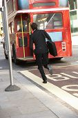 stock photo of running-late  - Businessman running for bus - JPG