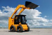 picture of skid-steer  - skid steer loader with full raised bucket outdoors - JPG