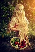 stock photo of natural blonde  - Beautiful young woman with magnificent blonde hair standing outdoor with a basket with apples - JPG