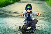stock photo of 7-year-old  - Cool 7 year old boy with his skateboard on the street - JPG