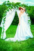 stock photo of wedding arch  - Beautiful bride with chaming red hair stands under the wedding arch - JPG