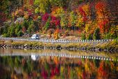 foto of camper-van  - Camper driving though fall forest with colorful autumn leaves reflecting in lake - JPG