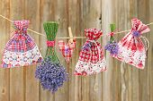 stock photo of sachets  - lavender and fragrant lavender sachets hanging on a leash in front of a wooden wall - JPG