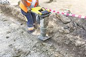 foto of vibration plate  - Worker uses compactor to firm soil at worksite - JPG