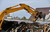 stock photo of asbestos  - A loader demolishes an old building to make way for a new bridge  - JPG