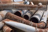 image of scrap-iron  - A stack of rusty and damaged industrial pipes and other metal products - JPG