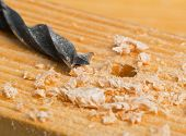 picture of wood craft  - Wood drill on wooden plank with wood chips selective focus on drill tip  - JPG