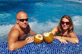 image of hot-tub  - Couple with coconut drink relaxing in hot tub - JPG