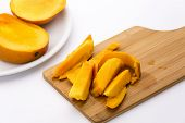 picture of flesh  - Four wedges of juicy mango fruit flesh separated from their peel lying on a wooden cutting board - JPG