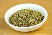 pic of oregano  - Dehydrated oregano macro in white bowl on wooden background - JPG