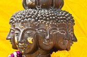 foto of metal sculpture  - Multi headed metallic buddha head on yellow background thailand - JPG
