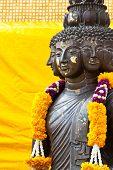 picture of metal sculpture  - Multi headed metallic buddha on yellow background thailand - JPG