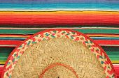 stock photo of mexican  - fiesta mexican poncho rug in bright colors with sombrero background with copy space cinco de mayo - JPG