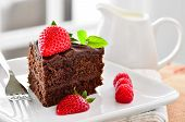 picture of chocolate fudge  - Fresh Home Made Sticky Chocolate Fudge Cake With Strawberries And Raspberries and a jug of fresh pouring cream - JPG
